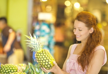 Happy woman buying fruit in grocery